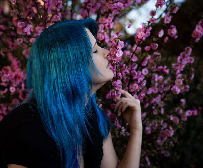 Dyed hair woman smelling flowers on plants at public park