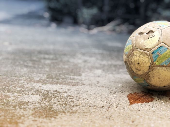 Close-up of abandoned soccer ball on road