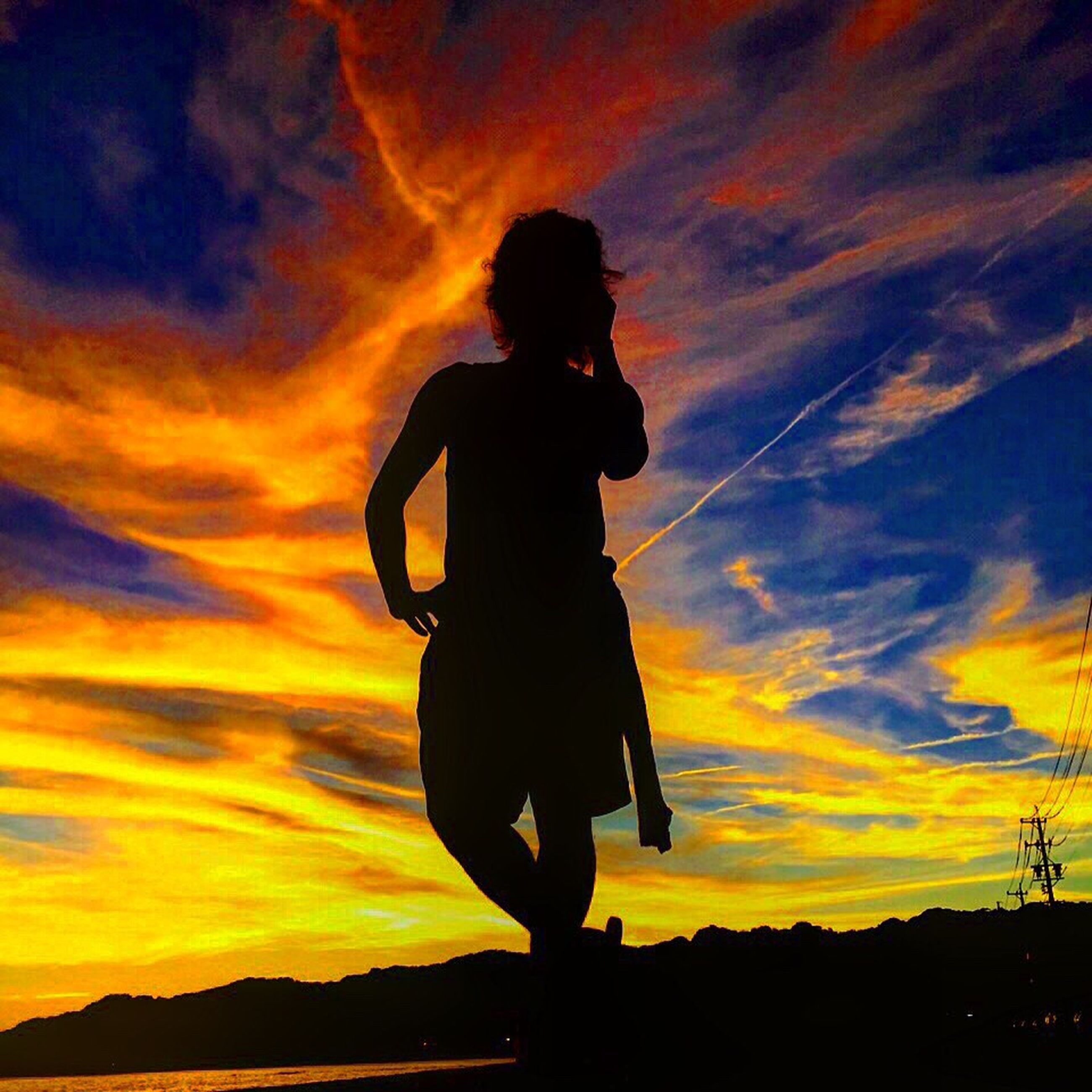 sunset, silhouette, sky, orange color, standing, lifestyles, leisure activity, cloud - sky, beauty in nature, full length, scenics, tranquil scene, three quarter length, tranquility, dramatic sky, nature, cloud, idyllic