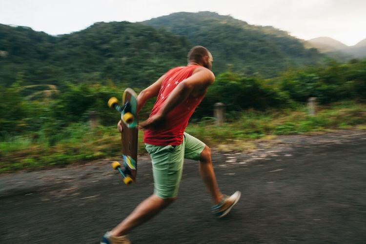 Full length of mid adult man skateboarding on mountain against sky