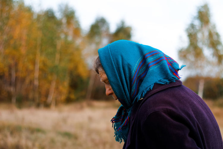 Portrait of russian grandmother senior old woman standing in yellow autumn park. old women in coat