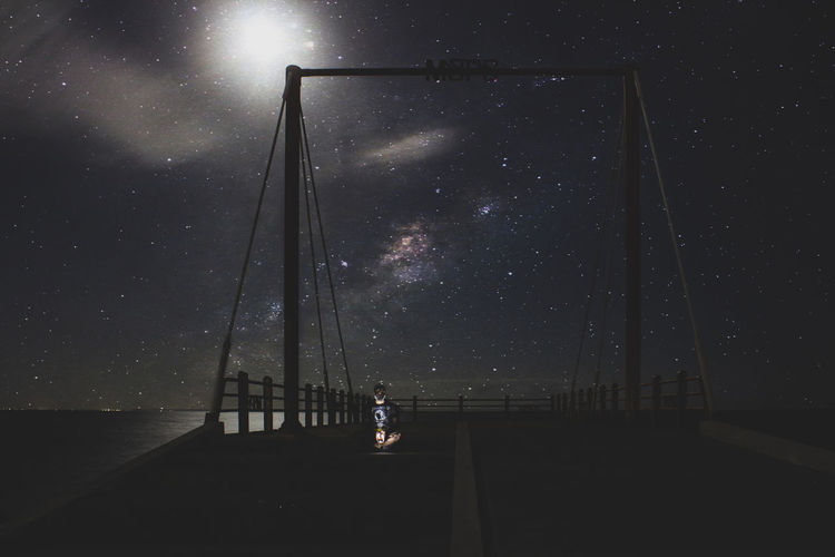 Rear view of silhouette man standing on bridge against sky at night
