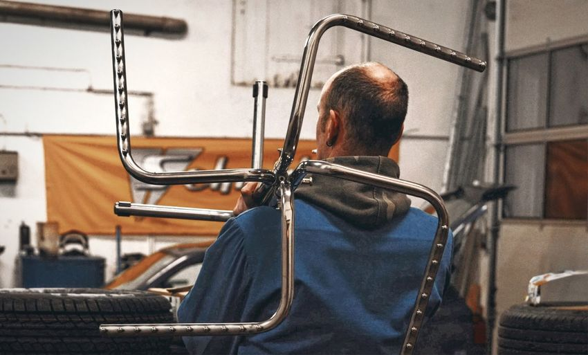 Rear view of mechanic holding chassis in workshop