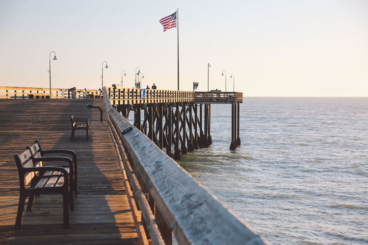 California Pacific Ventura Pier Beauty In Nature Clear Sky Day Flag Horizon Over Water Nature Ocean Outdoors Patriotism Pier Real People Sea Sky Sunset Tranquil Scene Water Wood - Material The Week On EyeEm California Dreamin Stay Out