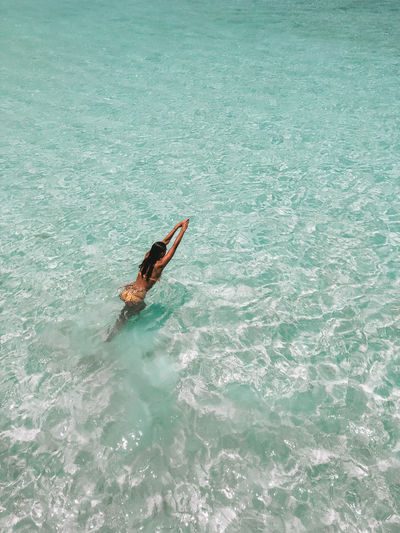 Flores INDONESIA Komodo Komodo National Park Pink Beach crystal clear Turquoise Water Paradise Beach Sea Water Girl Swimming Bikini Lifestyle One Person Leisure Activity Waterfront Real People High Angle View Day Nature Outdoors Travel Lifestyles Turquoise Colored Adventure