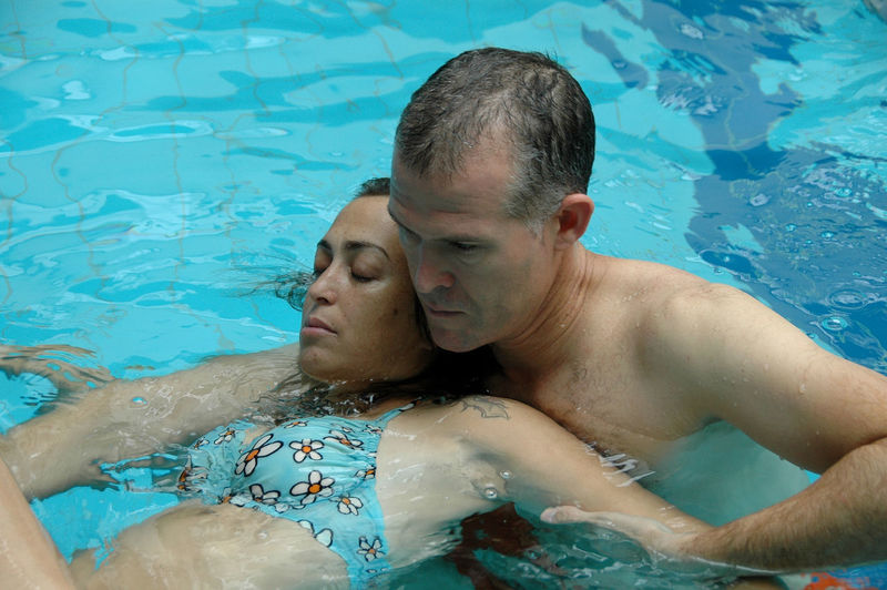 High angle view of mature man teaching young daughter swimming in pool