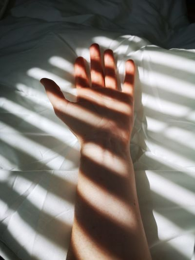 Close-up of human hand on bed
