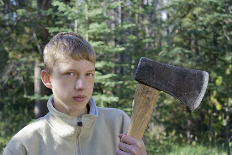 Portrait of teenage boy holding axe against trees in forest
