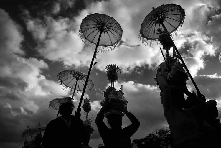 Low angle view of people with umbrella against cloudy sky during festival