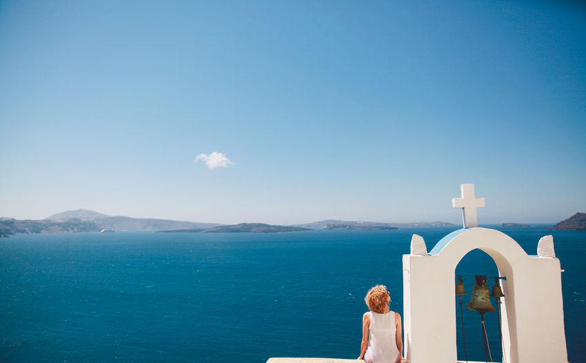 Rear view of woman sitting on church bell tower against aegean sea