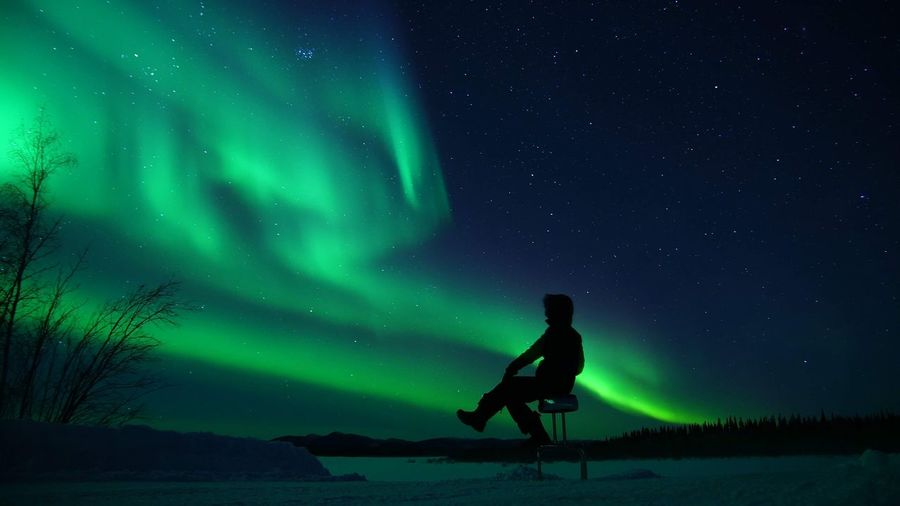 Man standing on snow against sky at night