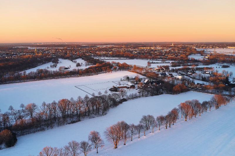 Drone view of landscape and fields in germany covered with snow during sunset