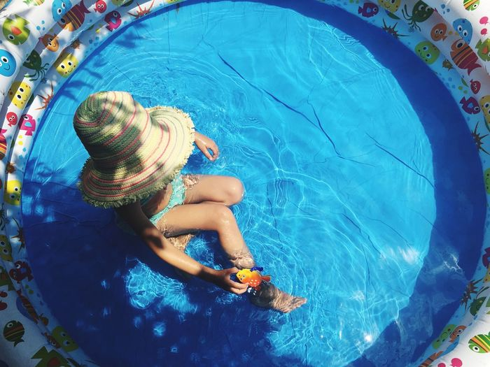 High Angle View Of Girl Wearing Sun Hat Sitting In Wading Pool On Sunny Day
