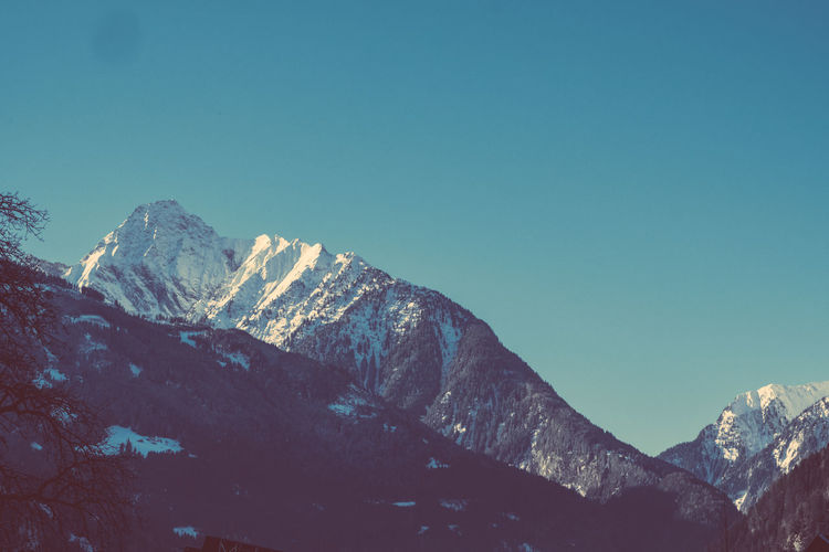 Low angle view of mountains against clear blue sky