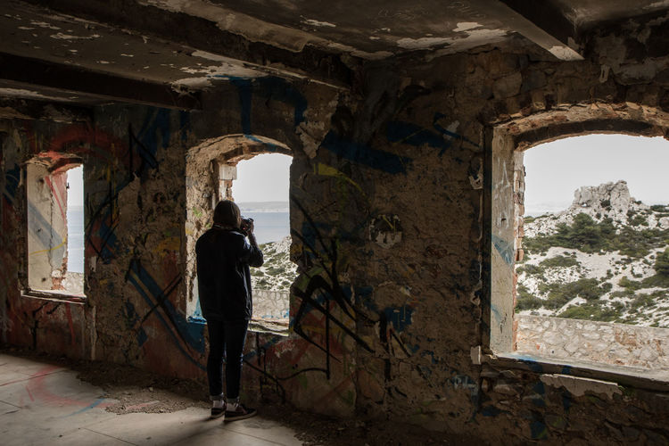 Rear view of man standing in abandoned building