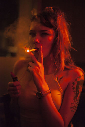 Portrait of young woman smoking in illuminated room