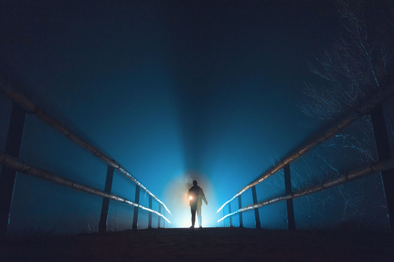 Person Standing On Illuminated Pathway Against Sky At Night