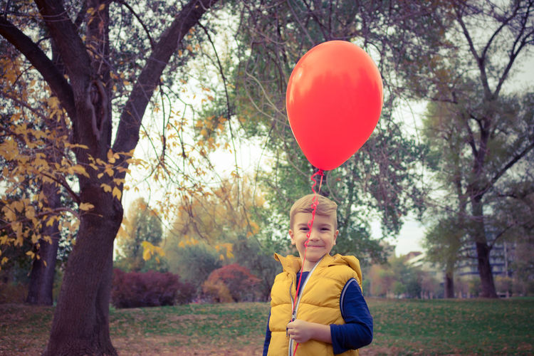 Balloon One Person Nature Casual Clothing Outdoors Boys Kid Childhood Child Children Only Playing Playful Helium Balloon Red Red Balloon Innocence Park - Man Made Space Autumn People Caucasian Blond Hair Carefree Cute Tree Portrait Park Looking At Camera Males  Happiness Smiling