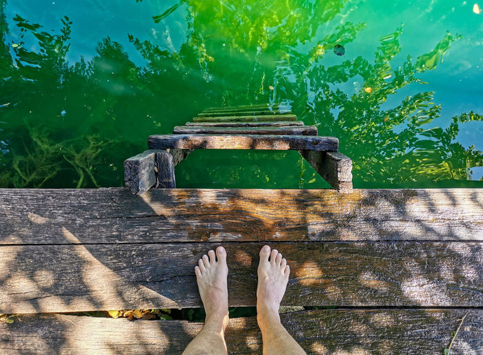 Low section of person on wooden walkway