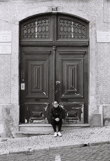 Full length of man sitting outside building