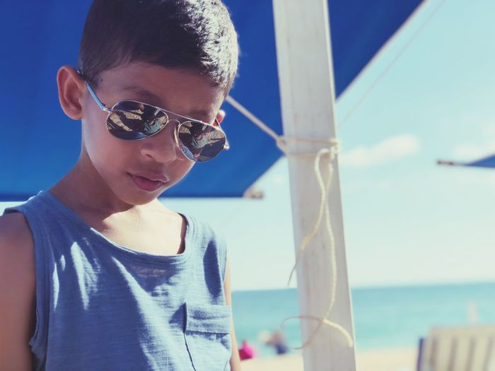 Portrait of boy wearing sunglasses while standing at beach