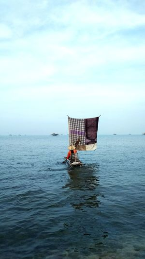 Rear view of man in boat with fabric at sea