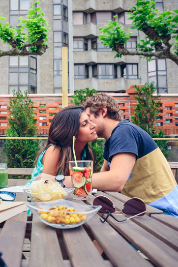 Man whispering in woman ear by food and drink at restaurant