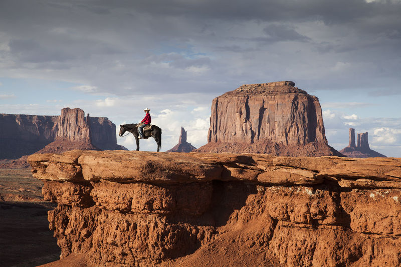 Rider at Monument Valley Cowboy Dramatic Sky Tourist Attraction  Wild West Beauty In Nature Cliff Cloud - Sky Day Domestic Animals Landscape Leisure Activity Mammal Men Nature One Person Outdoors People Physical Geography Real People Rock - Object Rock Formation Scenics Sky Sunset Travel Destinations