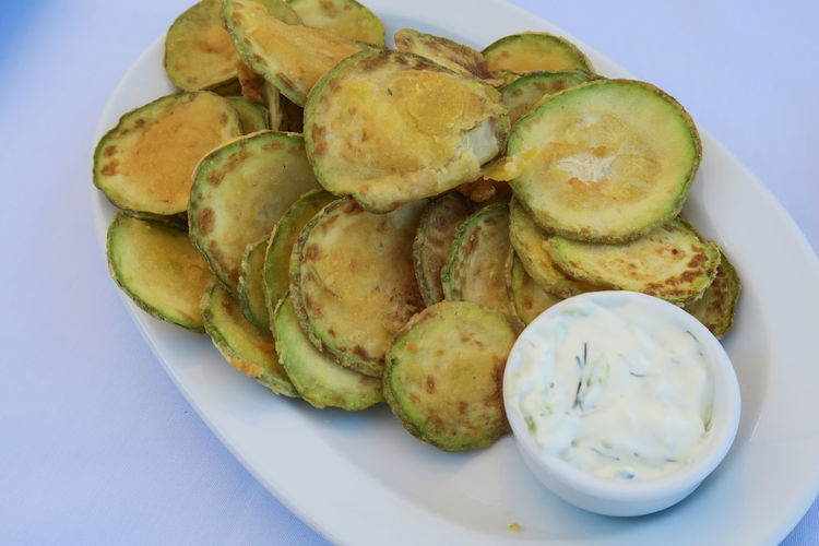 Fried zucchini chips with tzatziki Greek tavern plate. Floured zucchini are a dish commonly served at Greek tavernas, with a tzatziki sauce made of yogurt, cucumbers, salt, olive oil, and vinegar. Appetizing Food Chips Close-up Dish Floured Zucchini Food Fried Fried Zucchini Greek Food Greek Tavern Plate Herb Parsley Plate Prepared Ready-to-eat Selective Focus Serving Size Tasty Dishes Tzatziki Vegetable Vegetarian Vegetarian Food Vegetarian Lifestyle  Zucchini Zucchini Flower