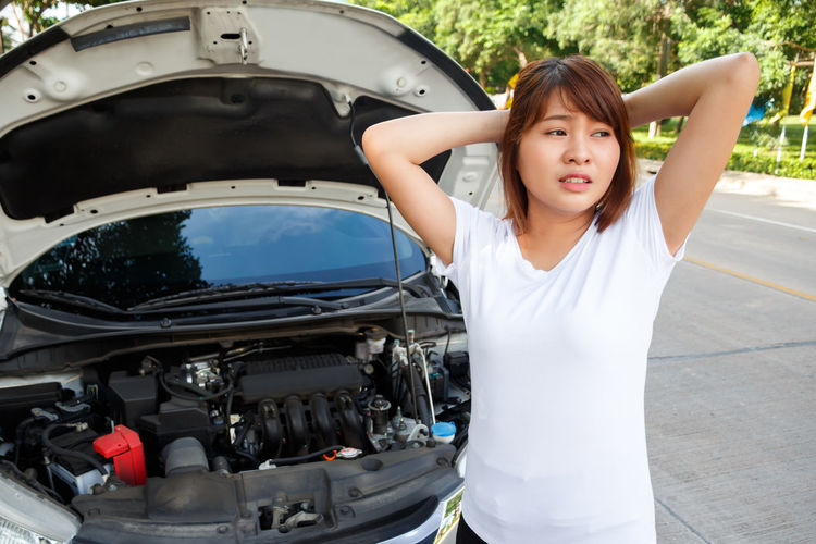 Young woman with hand in hair standing against broken down car on street