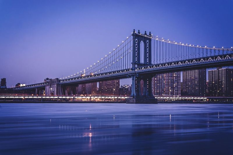 Low angle view of illuminated manhattan bridge over river against clear sky