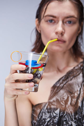 Portrait of young woman drinking water with plastics in glass