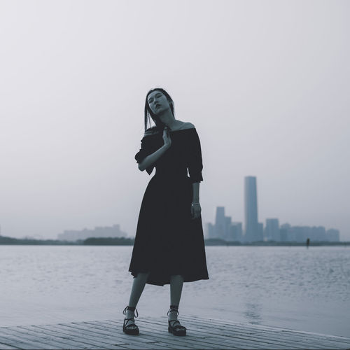 Full length of woman standing in city against sky