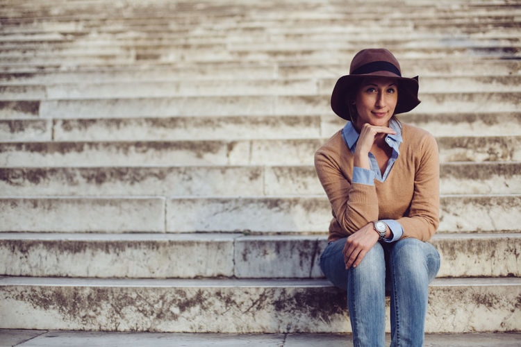 Portrait Of A Woman Stairs Adult Beautiful People Casual Clothing Clothing Contemplation Front View Hat Italian Jeans Leisure Activity Lifestyles Looking Males  Men One Person Real People Scarf Sitting Staircase Three Quarter Length Waiting Young Adult