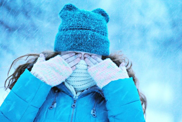 Girl Covering Eyes Against Sky During Snowfall