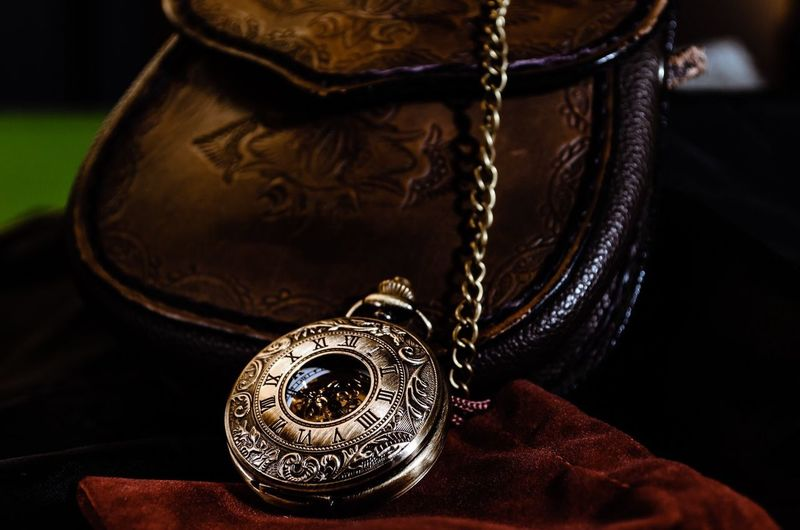 Close-up of pocket watch and bag against black background