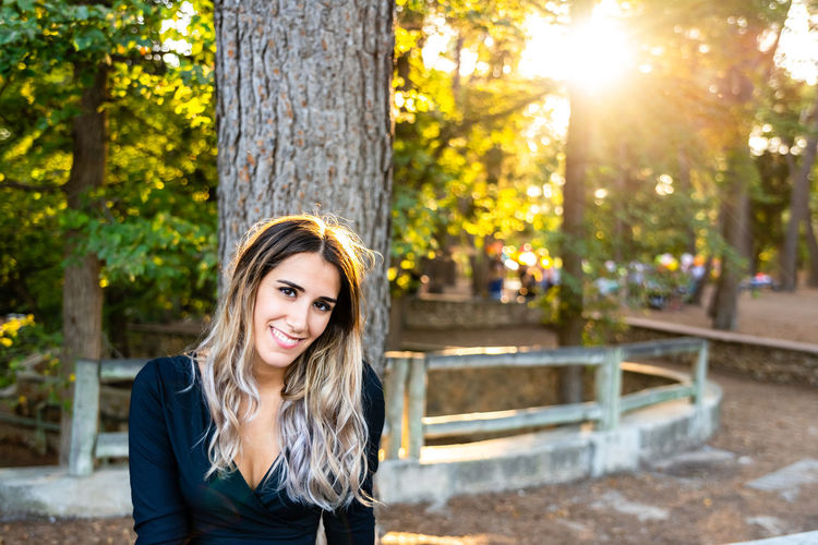 Portrait of smiling young woman against tree trunk at park