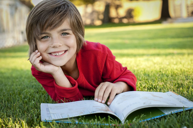 Portrait of smiling boy on book