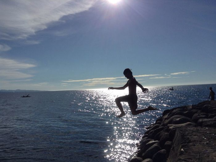 Silhouette person jumping in sea against cloudy sky
