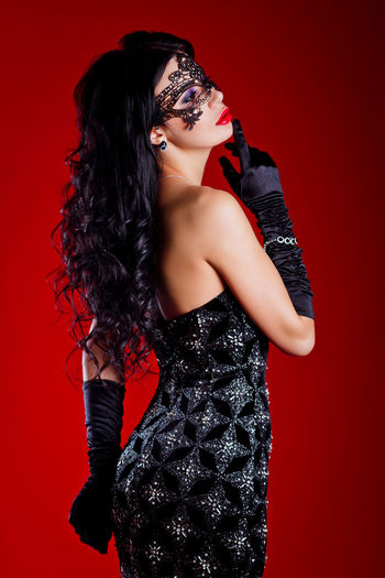 Fashion Model Wearing Mask Standing Against Red Background