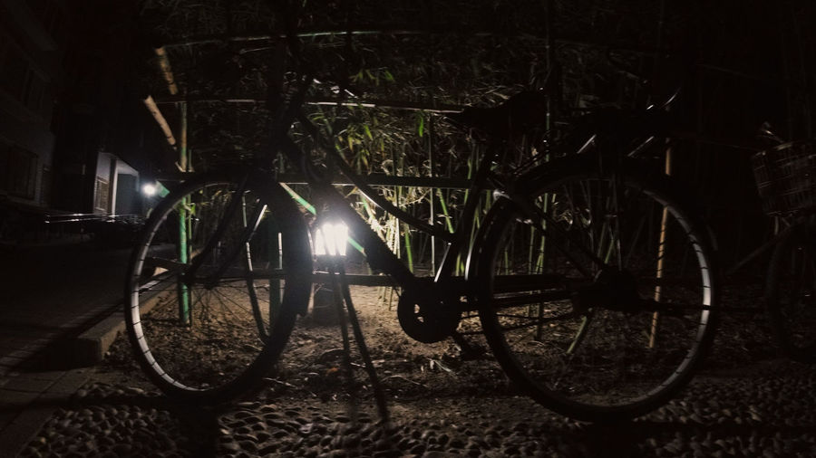Bicycle parked on street at night