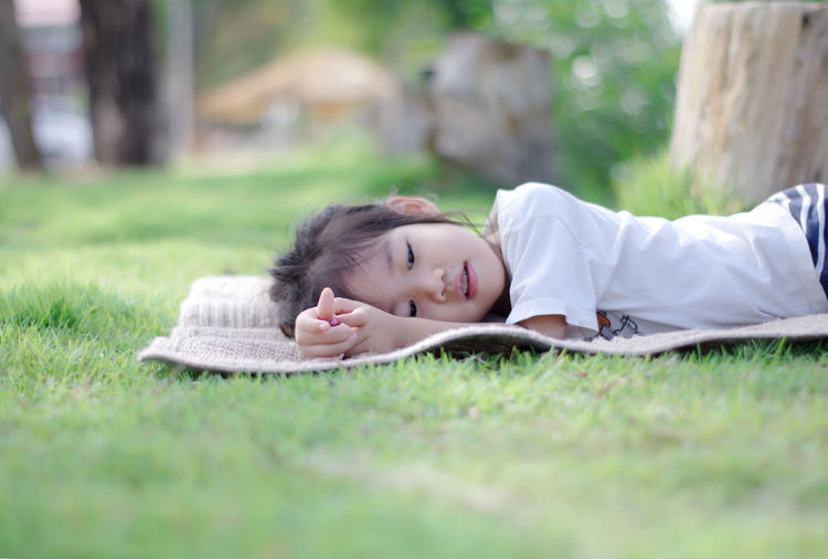 Cute girl lying on picnic blanket at park