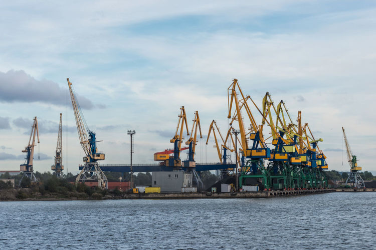 Taps row along the harbor shoreline. Business Container Cranes Harbor Transport Transportation Boat Cargo Cargo Container Coal Dock Equipment Export Import Logistic Material Mine Mineral Port Sea Ship Storage Terminal Vesel