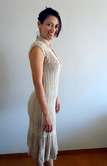 Portrait Of Smiling Young Woman Wearing Knitted Dress While Standing Against Wall At Home