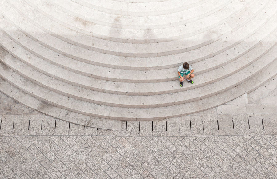 Boy On Steps Architecture Birds Eye View Boy Child Children Only Circular Circular Stairway Day Geometric Shape Geometry Innocence Isolated Light And Shadow Lonely Looking Down Lost Minimal Muted Colors Pensive Radial Shadow Stairs Steps Travel Urban Landscape #FREIHEITBERLIN