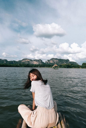 Smiling woman sitting on wooden raft over lake against sky