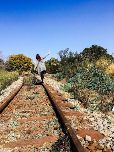 Rear View Of Woman Standing On Railroad Track Against Sky