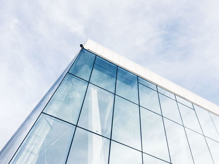 Low Angle View Of Modern Glass Office Building Against Sky