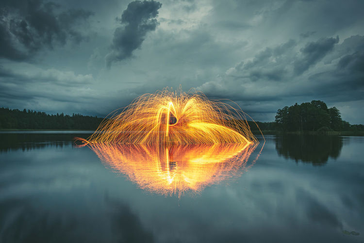 Woman With Wire Wool Over Lake Against Cloudy Sky