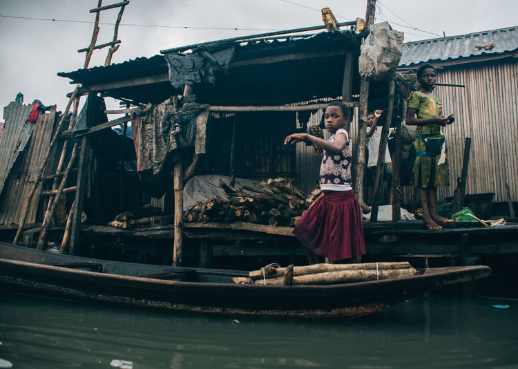Makoko Slum Adult Architecture Casual Clothing Clothing Day Front View Full Length Human Arm Mode Of Transportation Nature Nautical Vessel One Person Outdoors Real People Standing Transportation Water Women Young Adult Young Women